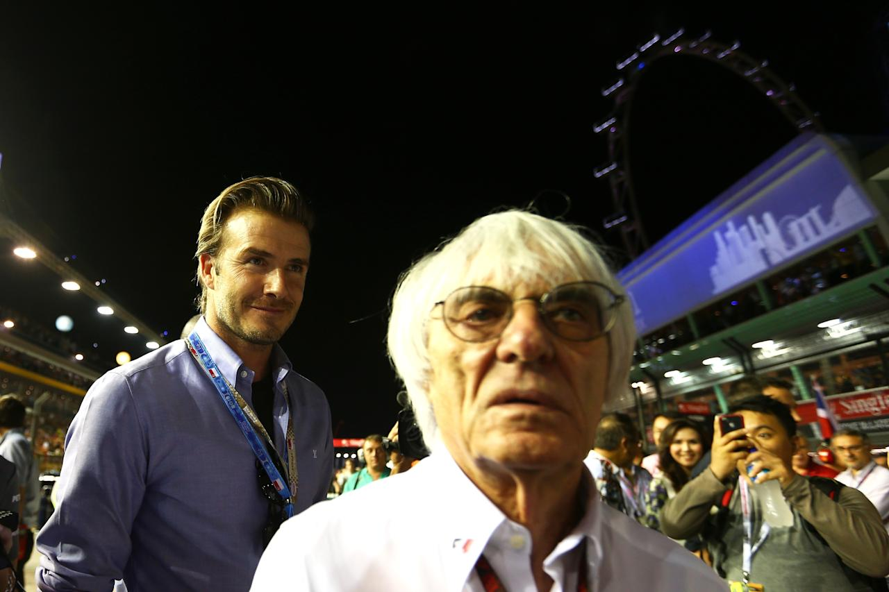 SINGAPORE - SEPTEMBER 22: F1 Supremo Bernie Ecclestone walks out onto the grid with his guest David Beckham during the Singapore Formula One Grand Prix at Marina Bay Street Circuit on September 22, 2013 in Singapore, Singapore.