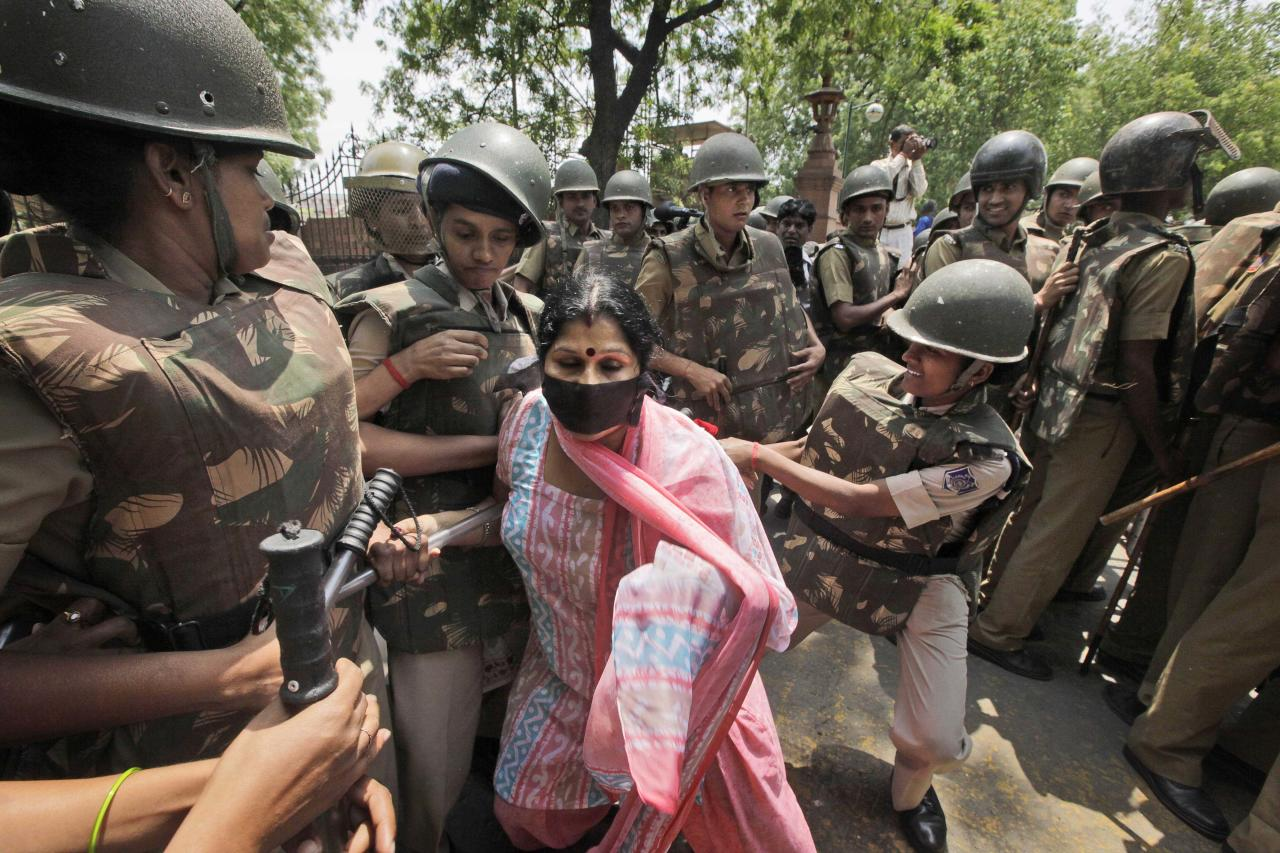 Indian policewomen detain a protester during a protest outside the Parliament in New Delhi, India, Monday, April 22, 2013. A second suspect was arrested Monday in the rape of a 5-year-old girl who New Delhi police said was left for dead in a locked room, a case that has brought a new wave of protests against how Indian authorities handle sex crimes. (AP Photo/Manish Swarup)