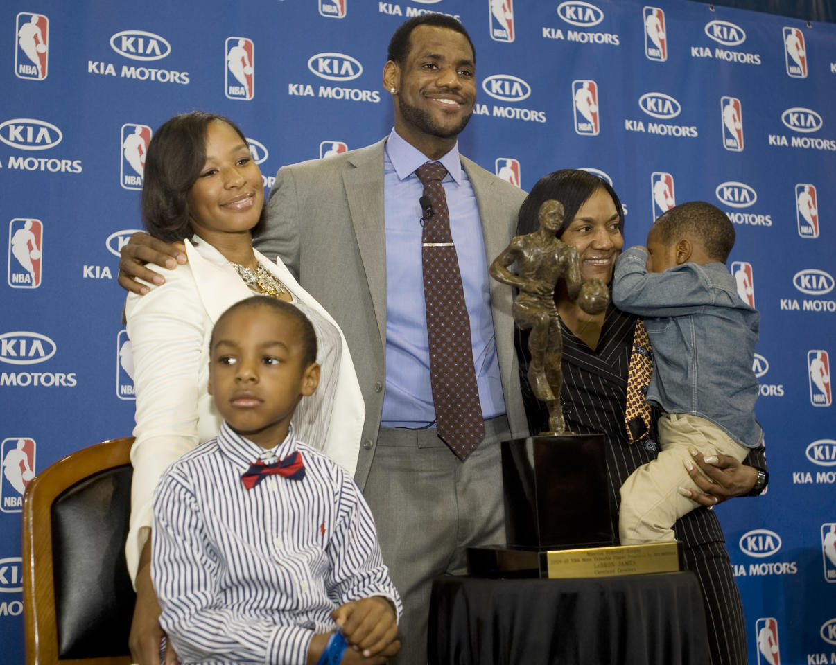 Cleveland Cavaliers forward and NBA Most Valuable Player LeBron James, center, stands with his family, girfriend, Savannah Brinson, left, in white, son, LeBron Jr., foreground left, James mother Gloria, right, holding James son Bryce, after the NBA MVP award ceremony for James on the University of Akron campus in Akron, Ohio, Sunday, May 2, 2010. (AP Photo/Phil Long)