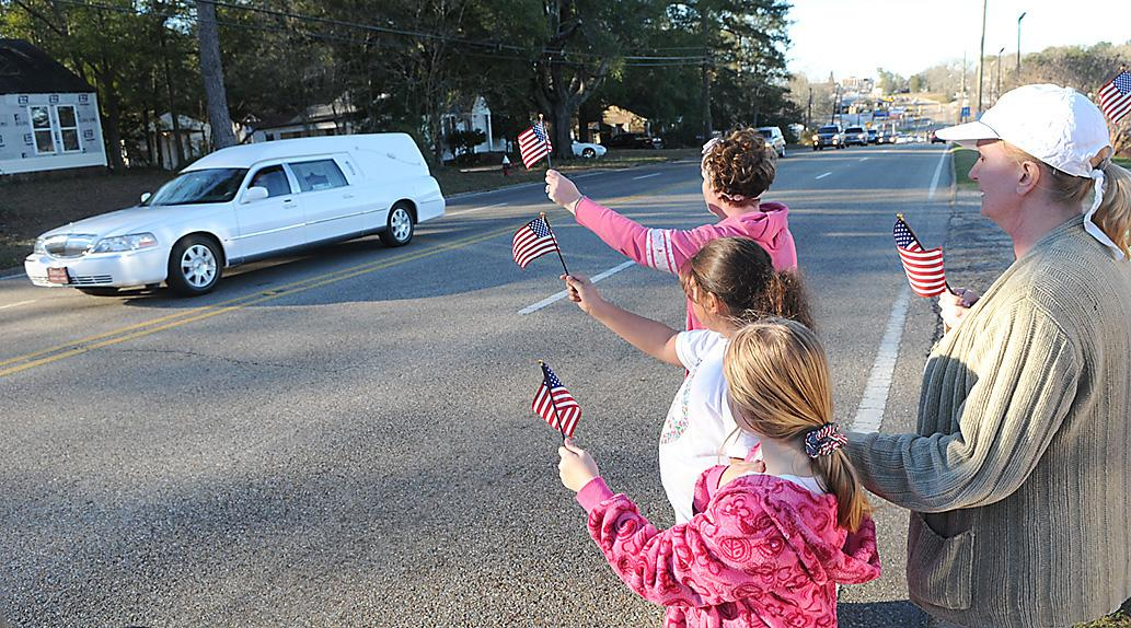 """Residents raise flags along the processional route in Ozark for Dale County Schools bus driver Charles """"Chuck"""" Poland Jr., who died Tuesday, in Ozark, Ala., Sunday, Feb. 3, 2013. Authorities say Jim Lee Dykes, 65 — a decorated veteran of the Vietnam War known as Jimmy to neighbors — gunned down Poland, a school bus driver, and then abducted a 5-year-old boy from the bus, taking him to an underground bunker on his rural property. (AP Photo/Dothan Eagle, Danny Tindell)"""