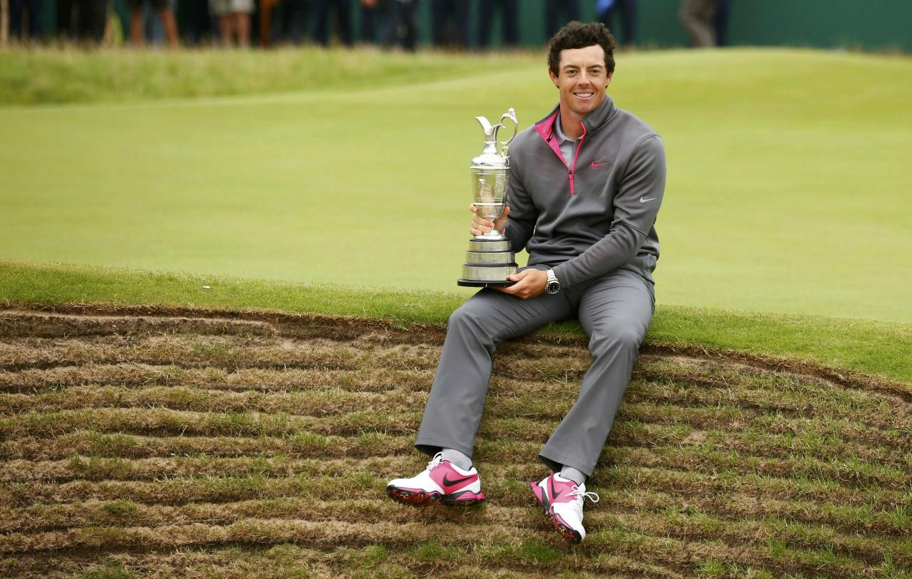 Rory McIlroy of Northern Ireland sits on the edge of a bunker as he holds the Claret Jug after winning the British Open Championship at the Royal Liverpool Golf Club in Hoylake, northern England July 20, 2014. REUTERS/Cathal McNaughton (BRITAIN - Tags: SPORT GOLF)