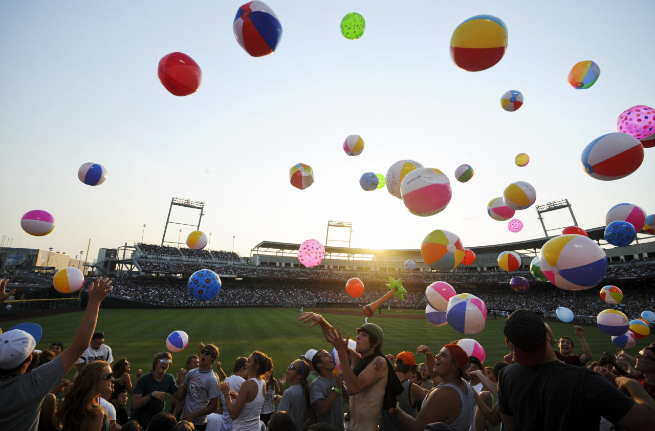 Fans play with beach balls and other inflatable objects in the fourth inning of Game 2 of the NCAA College World Series baseball finals between Arizona and South Carolina in Omaha, Neb., Monday, June 25, 2012. (AP Photo/Dave Weaver)