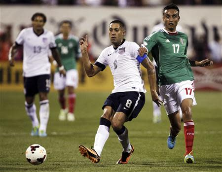 United States' Dempsey passes the ball under pressure from Mexico's Zavala during the first half of their 2014 World Cup qualifying soccer match in Columbus