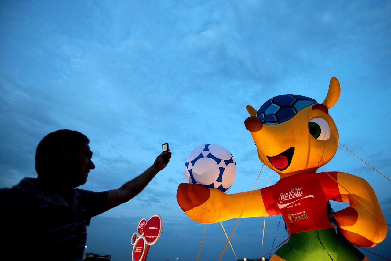 A man takes pictures of the mascot of the 2014 World Cup soccer tournament in Brasilia, Brazil, Monday, Sept. 24, 2012. The mascot is a yet to-be-named Brazilian endangered armadillo. FIFA said Brazilians will have until mid-November to choose the mascot's name from three choices: Amijubi, Fuleco and Zuzeco. (AP Photo/Eraldo Peres)