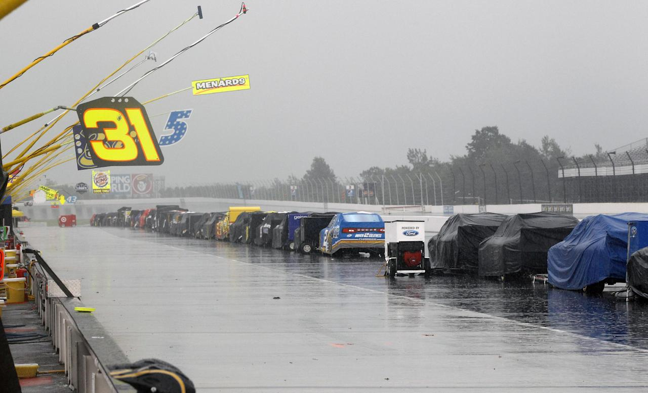 Race cars sit covered along the pits after the start of the NASCAR Sprint Cup Series auto race was postponed due to rain on Sunday, Aug. 5, 2012, at Pocono Raceway in Long Pond, Pa. (AP Photo/Mel Evans)