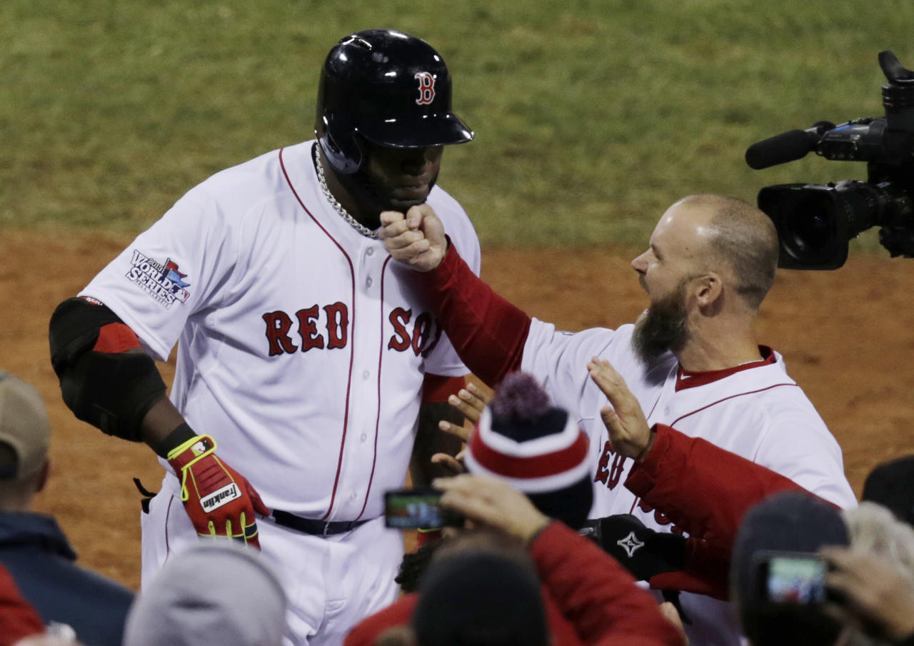 Boston Red Sox's David Ross tugs on the beard of David Ortiz, left, after Ortiz hit a two-run home run in the seventh inning of Game 1 of baseball's World Series against the St. Louis Cardinals Wednesday, Oct. 23, 2013, in Boston. (AP Photo/Charles Krupa)