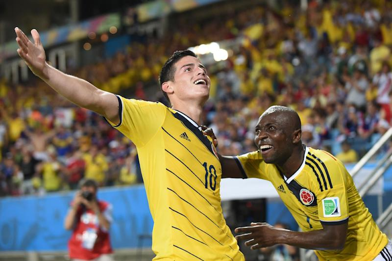 Colombia's midfielder James Rodriguez (L) celebrates with his teammate defender Pablo Armero after scoring at the Pantanal Arena in Cuiaba during the 2014 FIFA World Cup on June 24, 2014