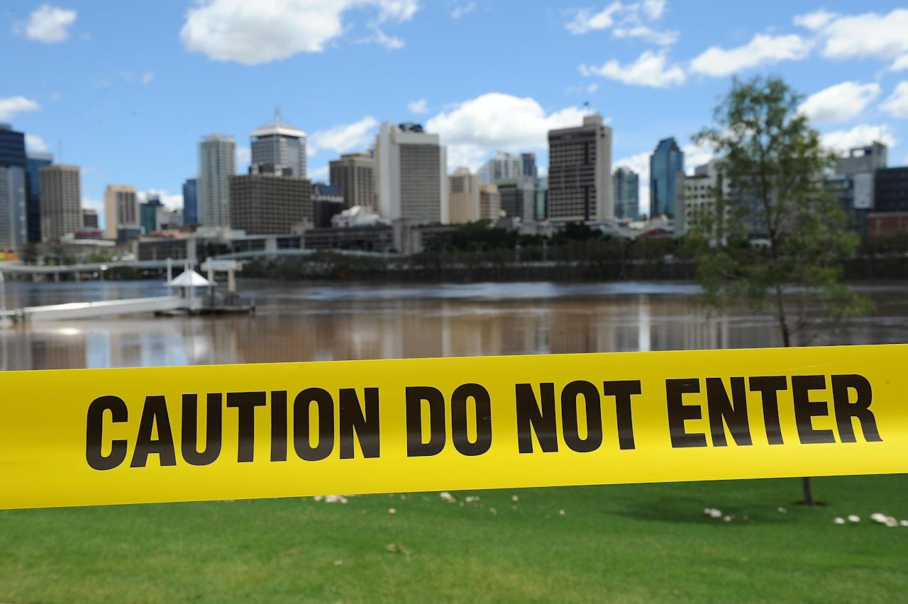 BRISBANE, AUSTRALIA - JANUARY 29: Council caution tape is seen to restrict access to the Brisbane river at South Bank as parts of southern Queensland experiences record flooding in the wake of Tropical Cyclone Oswald on January 29, 2013 in Brisbane, Australia. The river in the Brisbane CBD is expected to peak at 2.3 metres today - lower than the 2.6 metre peak predicted - but is still likely to flood low-lying properties and businesses. The flood crisis has claimed four lives so far, with the city of Bundaberg, Queensland faces the worst flooding in its history. (Photo by Matt Roberts/Getty Images)