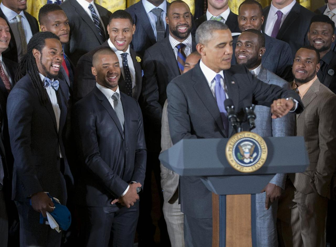 Seattle Seahawks cornerback Richard Sherman, left, and quarterback Russell Wilson, second from left, laugh as President Barack Obama looks at his watch as he comments about Sherman during a ceremony in the East Room of the White House in Washington, Wednesday, May 21, 2014, welcoming the NFL Super Bowl champion Seattle Seahawks football team. The Seahawks defeated the Denver Broncos in Super Bowl XLVIII. (AP Photo/Pablo Martinez Monsivais)