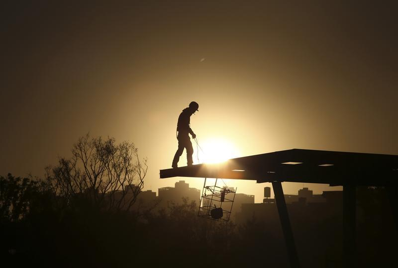A construction worker stands on a rooftop near a residential compound in Kunming