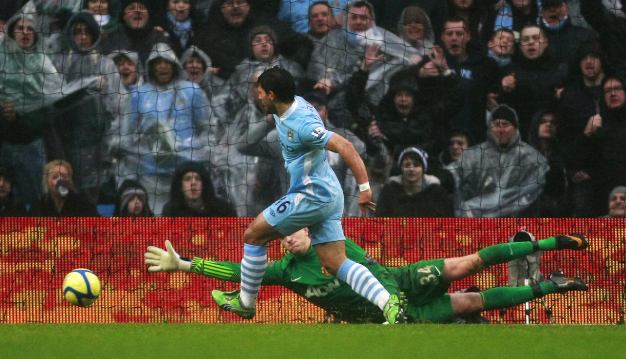 Manchester City's Sergio Aguero, left, beats Manchester United goalkeeper Anders Lindegaard to score a goal during their FA Cup third round soccer match at Etihad Stadium, Manchester, England, Sunday, Jan. 8, 2012. (AP Photo/Tim Hales)
