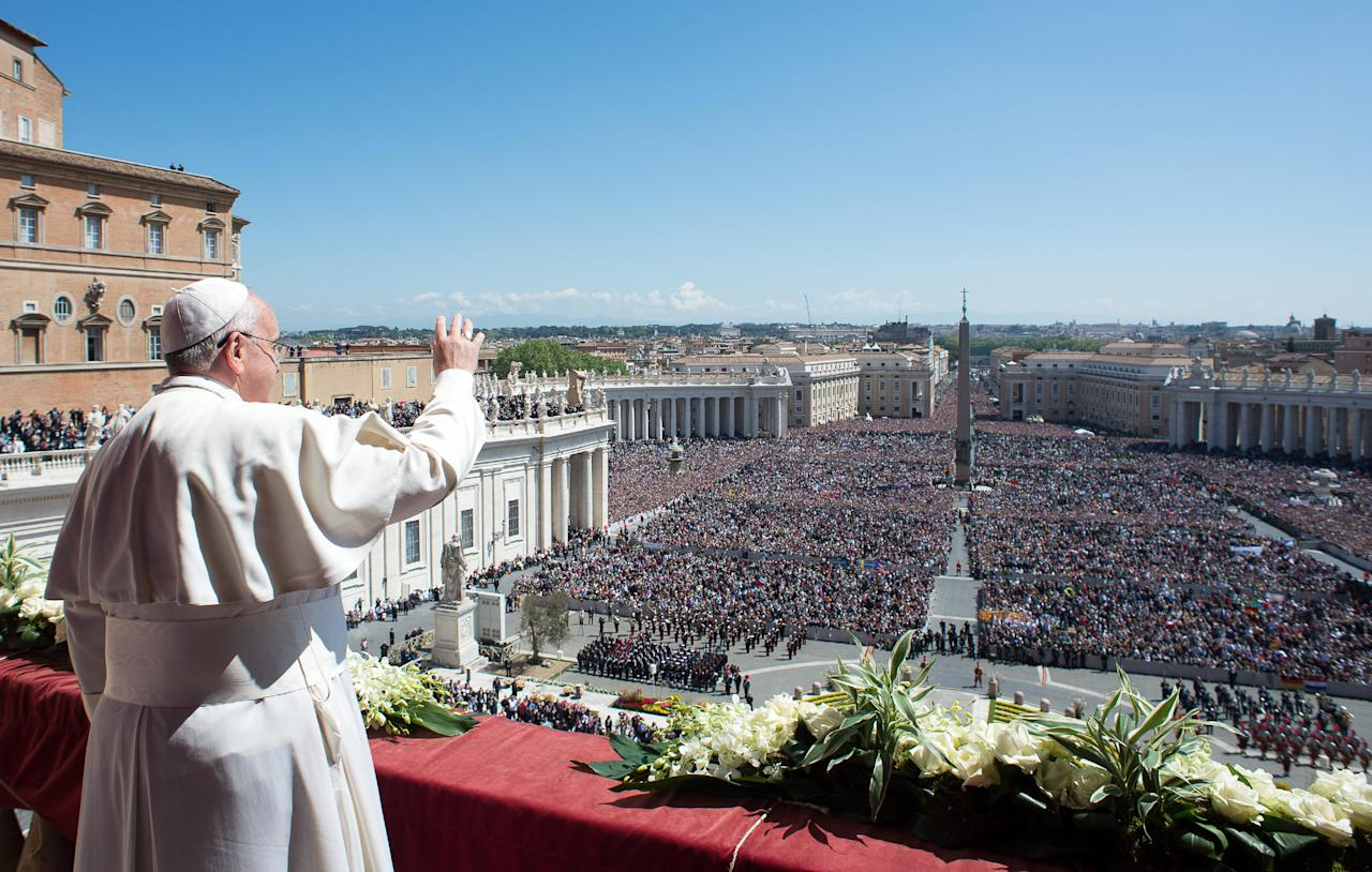 In this photo provided by the Vatican newspaper L'Osservatore Romano, Pope Francis waves to the crowd from the balcony of St. Peter's Basilica where he delivered the Urbi et Orbi (Latin for to the city and to the world) at the end of the Easter Mass in St. Peter's Square at the the Vatican Sunday, April 20, 2014. (AP Photo/L'Osservatore Romano, ho)