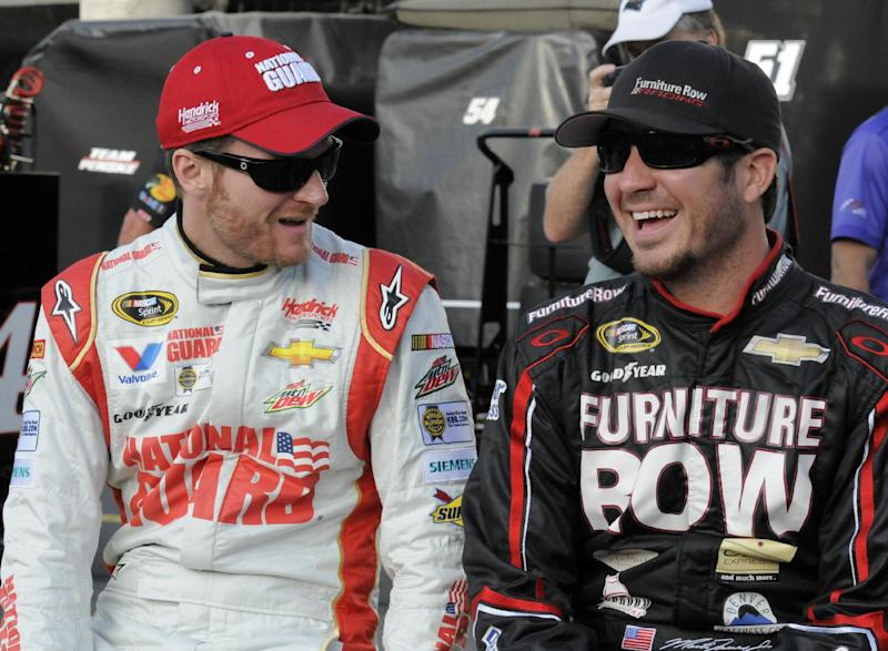 Dale Earnhardt Jr, left, talks with Martin Truex Jr, before qualifying for Sunday's NASCAR Sprint Cup series auto race at Charlotte Motor Speedway in Concord, N.C., Thursday, May 22, 2014