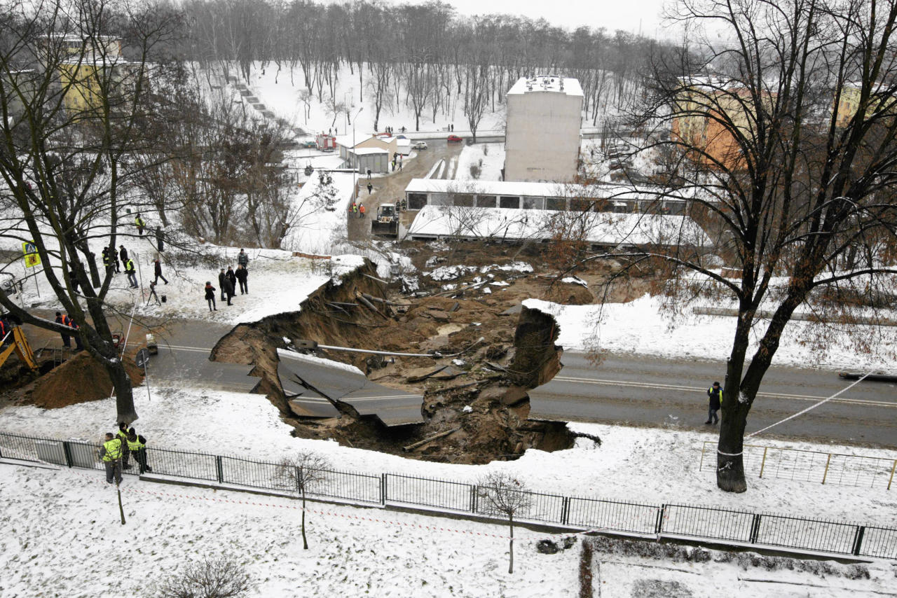 Onlookers examine the damage after a section of a road collapsed in Ostrowiec Swietokrzyski, southern Poland December 19, 2012. A hole, measuring 10 metres (33 ft) deep and at least 50 metres (164 ft) wide, appeared on a road in Ostrowiec Swietokrzyski over Tuesday night, reported by local media. REUTERS/Pawel Malecki/Agencja Gazeta (POLAND - Tags: ENVIRONMENT DISASTER) FOR EDITORIAL USE ONLY. NOT FOR SALE FOR MARKETING OR ADVERTISING CAMPAIGNS. THIS IMAGE HAS BEEN SUPPLIED BY A THIRD PARTY. IT IS DISTRIBUTED, EXACTLY AS RECEIVED BY REUTERS, AS A SERVICE TO CLIENTS. POLAND OUT. NO COMMERCIAL OR EDITORIAL SALES IN POLAND - RTR3BQS5