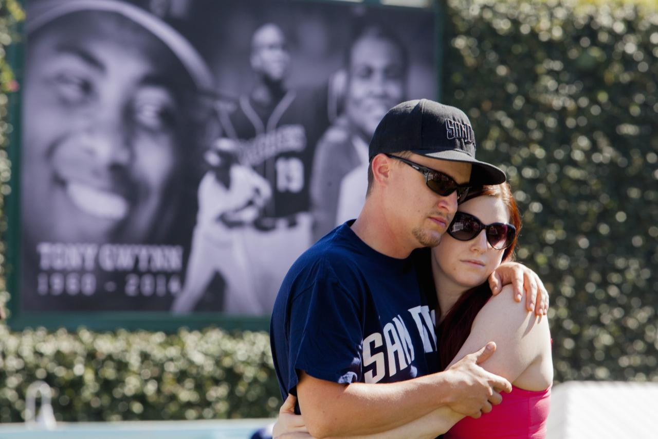 Kenny Funk, 26, embraces his girlfriend Carrie Poole, 25, at a makeshift memorial to former San Diego Padres outfielder Tony Gwynn at Petco Park in San Diego, California June 16, 2014. Gwynn, one of the greatest hitters of his generation, died on Monday at age 54 after a battle with cancer, the National Baseball Hall of Fame and Museum said. REUTERS/Sam Hodgson (UNITED STATES - Tags: SPORT BASEBALL OBITUARY)
