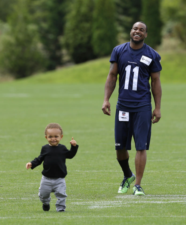Seattle Seahawks wide receiver Percy Harvin, right, laughs as his son Jaden, 1, as he runs on the field following the final day of NFL football training camp, Wednesday, Aug. 13, 2014, in Renton, Wash. (AP Photo/Ted S. Warren)