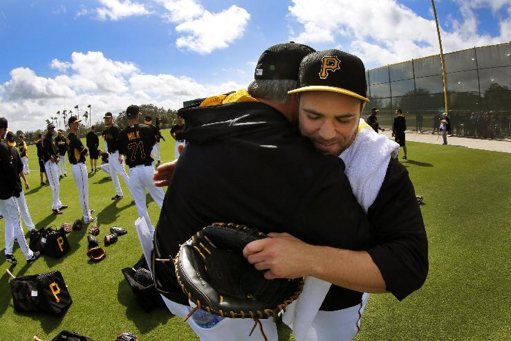 Pittsburgh Pirates manager Clint Hurdle, left, hugs catcher Russell Martin, right, as he arrives for the team's first day of baseball spring training for pitchers and catchers, in Bradenton, Fla., Thursday, Feb. 13, 2014. (AP Photo/Gene J. Puskar)