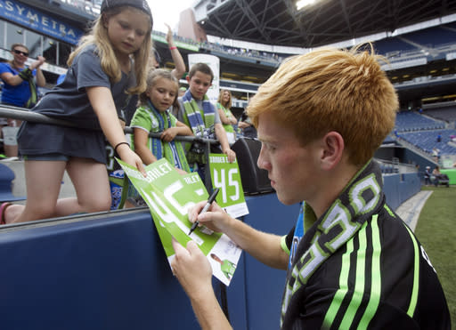Seattle Sounders' Xander Bailey signs autographs for fans following a friendly soccer match against Tottenham Hotspur in Seattle, Saturday, July 19, 2014. The matched ended in a 3-3 draw. Bailey was signed to the Sounders for the match as part of the Make-A-Wish program. (AP Photo/Stephen Brashear)
