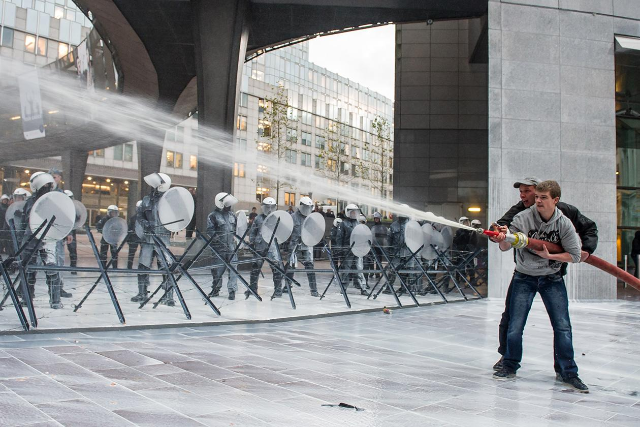 Police officers, left, are sprayed with milk by European milk farmers during a demonstration outside the European Parliament in Brussels.