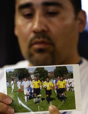 A relative holds up a photo of Ricardo Portillo in action — Associated Press