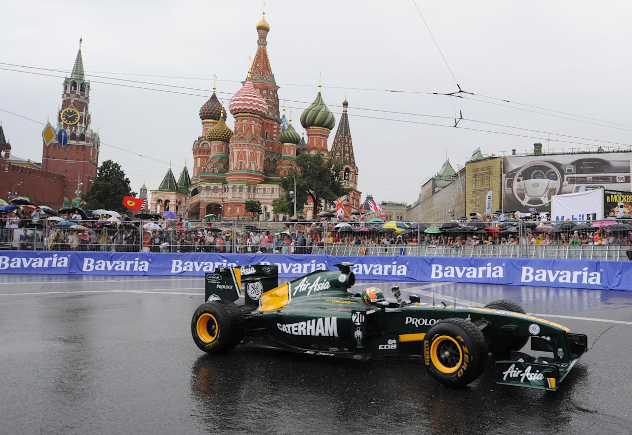 "Formula One Team Lotus driver Karun Chandhok of India drives past St. Basils cathedral during the ""Moscow City Racing"" show on July 17, 2011 in central Moscow. AFP PHOTO / NATALIA KOLESNIKOVA (Photo credit should read NATALIA KOLESNIKOVA/AFP/Getty Images)"