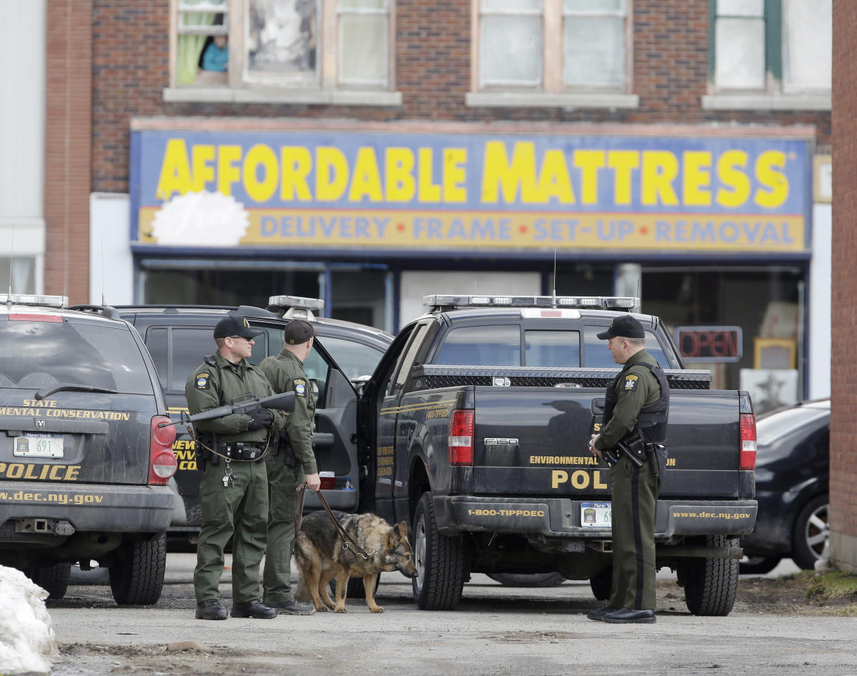 Law enforcement officers stand in an alley near Main Street while searching for a suspect in two shootings that killed four and injured at least two on Wednesday, March 13, 2013. Authorities were looking for Kurt Meyers, said Joseph Malone, the police chief for Herkimer and Mohawk. Officials say guns and ammunition were found inside his Mohawk apartment after emergency crews were sent to a fire there Wednesday morning. (AP Photo/Mike Groll)