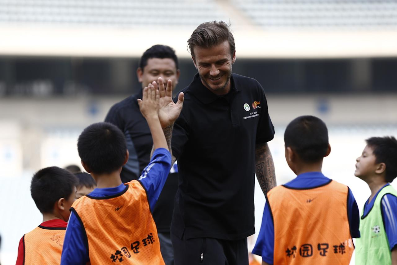 NANJING, CHINA - JUNE 18:  (CHINA OUT) David Beckham plays football with young fans at at Nanjing Olympic Sports Center on June 18, 2013 in Nanjing, China.  (Photo by ChinaFotoPress/ChinaFotoPress via Getty Images)