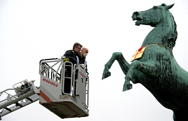 A firefighter and a police officer look at a golden Leibniz cookie that hangs from a horses neck in front of the Leibniz University in Hannover, Germany,  Tuesday Feb. 5, 2013.  It is still not clear if the cookie belongs to the Bahlsen House, which reported theft in January. Someone dressed as the Cookie Monster has sent  blackmails regarding the  stolen cookie sculptur, The gilded bronze item was part of a statue outside German cookie baker Bahlsen's Hannover office, and it was reported stolen last month.The thief demanded that cookies be delivered to children at a city hospital.  (AP Photo/dpa, Jochen Luebke)