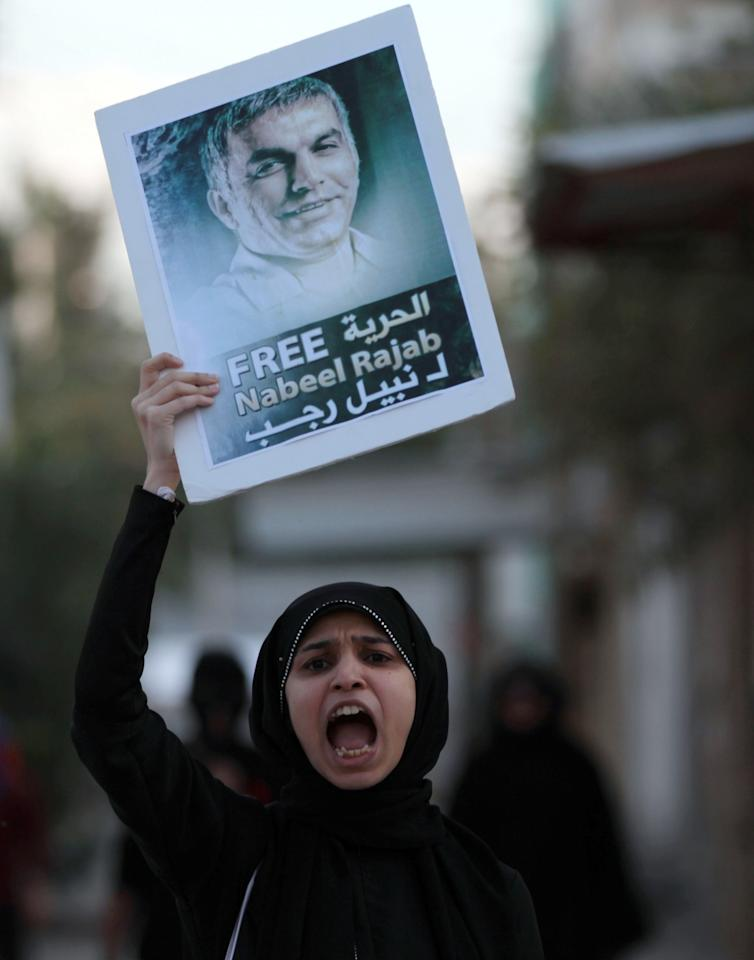 A Bahraini anti-government protester chants slogans as she holds up a pictures of jailed human right activist Nabeel Rajab, toward riot police during clashes in Abu Saiba, Bahrain, Monday, Dec. 3, 2012. (AP Photo/Hasan Jamali)