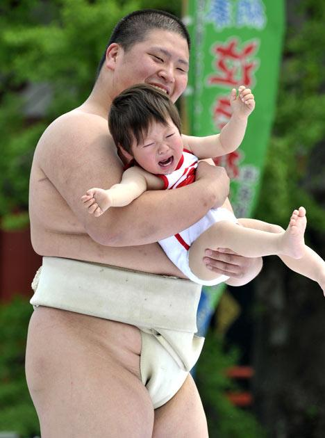 """A crying baby is carried by a student sumo wrestler during the """"Baby-cry Sumo"""" competition at Tokyo's Sensoji temple on April 30, 2011.  Some 50 babies aged under one participated in the annual baby crying contest. Japanese parents believe that sumo wrestlers can help make babies cry out a wish to grow up with good health.   AFP PHOTO/Yoshikazu TSUNO"""