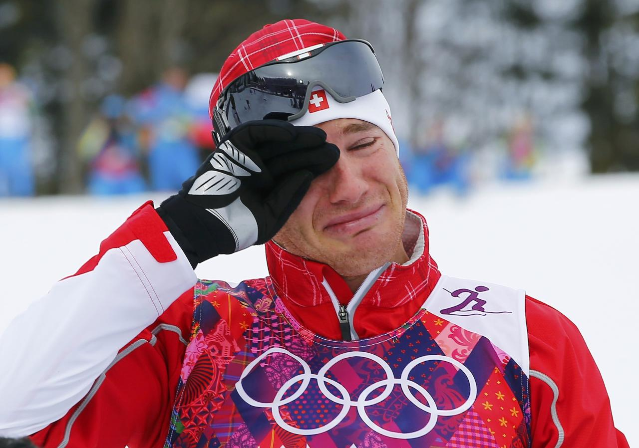 Winner Dario Cologna of Switzerland reacts during the flower ceremony for the men's skiathlon event at the Sochi 2014 Winter Olympics in Rosa Khutor February 9, 2014. REUTERS/Carlos Barria (RUSSIA - Tags: SPORT OLYMPICS SPORT SKIING)