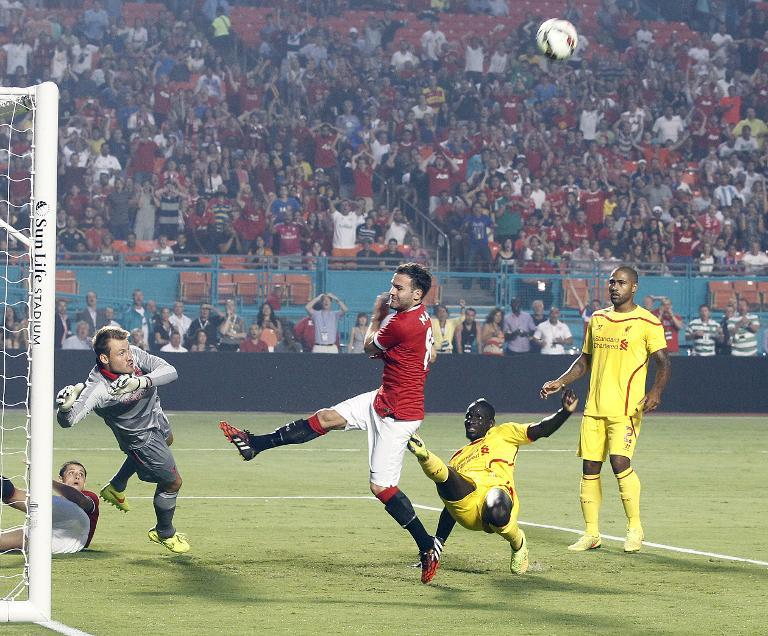 A shot by Manchester United's Juan Mata (C) is stopped by Liverpool goalkeeper Simon Mignolet during the International Champions Cup friendly match at Sun Life Stadium on August 4, 2014