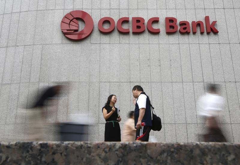 Office workers pass a logo of Overseas-Chinese Banking Corp Ltd (OCBC) at the company's headquarters in Singapore