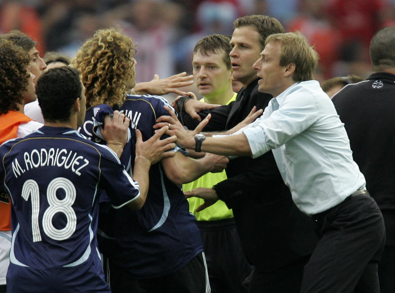 The June 30, 2006 file photo shows then German coach Juergen Klinsmann, right, and  team manager Oliver Bierhoff, second from right, holding back Argentina player Fabricio Coloccini after Germany's 4-2 shootout win in the quarterfinal World Cup soccer match between Germany and Argentina at the Olympic Stadium in Berlin. On Sunday, July 13, 2014, Germany and Argentina will face each other again in the final of the 2014 soccer World Cup