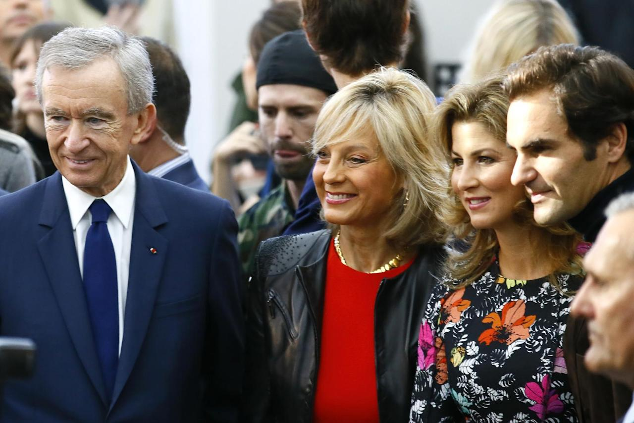 Swiss tennis player Roger Federer, right, his wife Mirka, second right, French luxury group Chairman and CEO Bernard Arnault , left, his wife Helene Mercier smile during Louis Vuitton's Spring-Summer 2017 ready-to-wear fashion collection presented Wednesday, Oct. 5, 2016 in Paris. (AP Photo/Francois Mori)