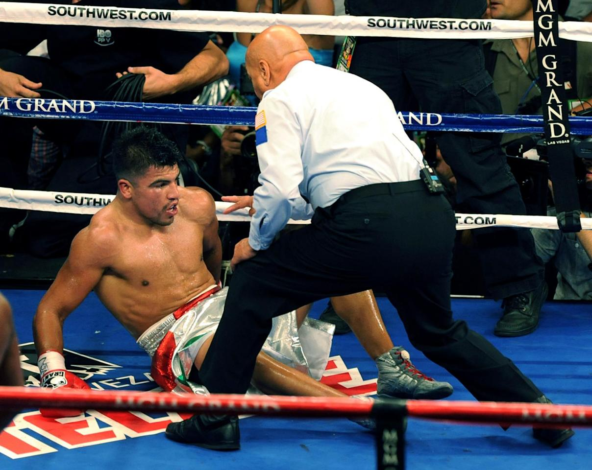 In this photo provided by the Las Vegas News Bureau, referee Joe Cortez checks on Victor Ortiz during a WBC Welterweight boxing bout against Floyd Mayweather, Saturday, Sept. 17, 2011, in Las Vegas. Mayweather won by a knockout in the fourth round. (AP Photo/Las Vegas News Bureau, Brian Jones)