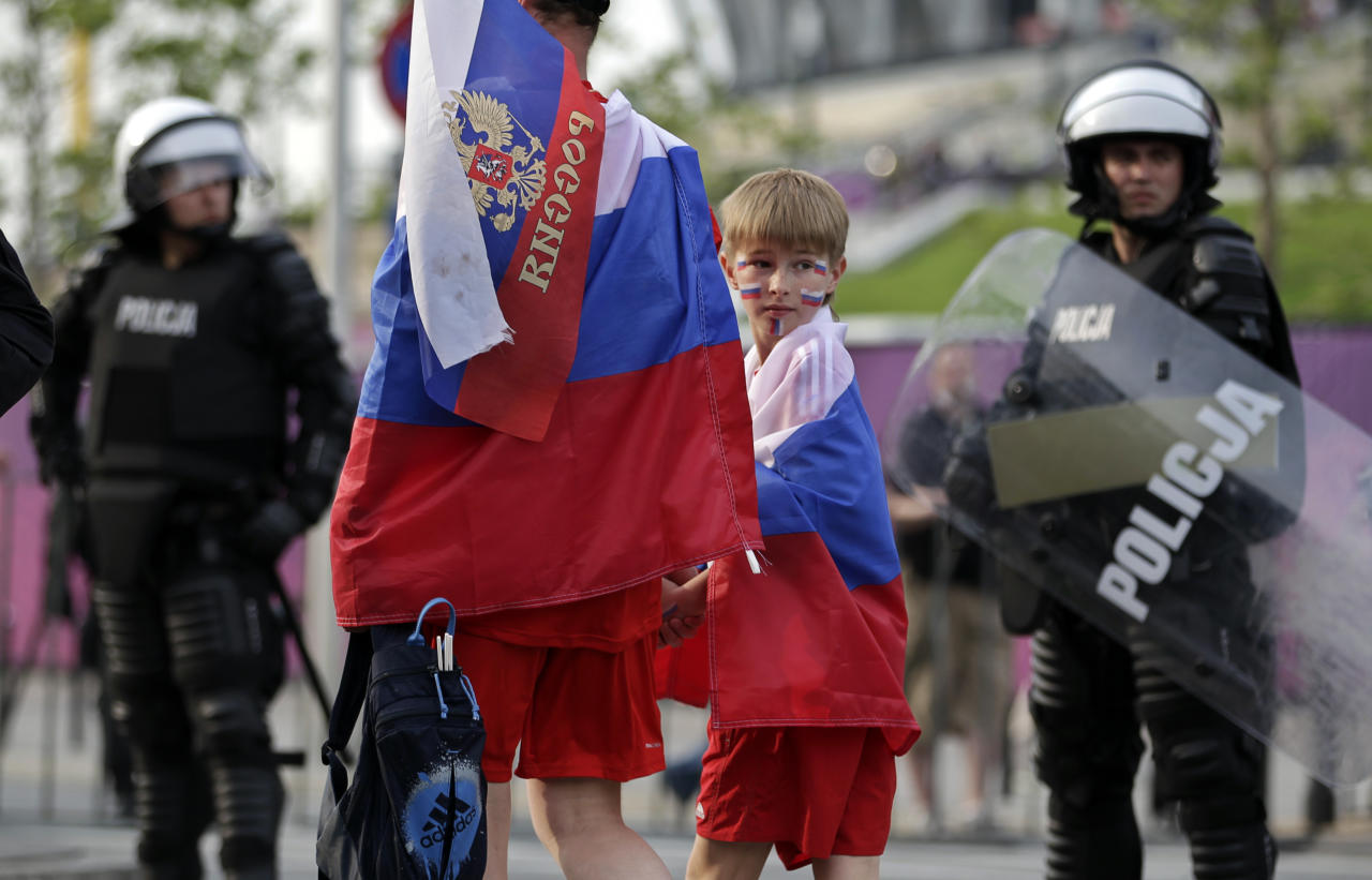 Russian fans arrive under heavy security prior to the Euro 2012 soccer championship Group A match between Poland and Russia in Warsaw, Poland, Tuesday, June 12, 2012. Russian soccer fans clashed with police and Poland supporters in separate incidents in Warsaw on Tuesday, just hours before the two teams were to meet in an emotionally charged European Championship match. Several people were injured. (AP Photo/Gero Breloer)