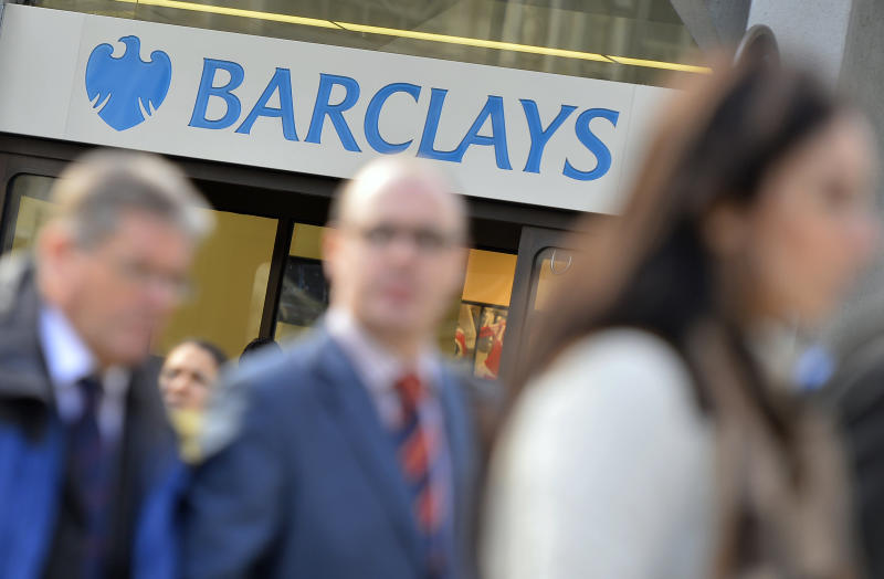 People walk past a branch of Barclays bank in London
