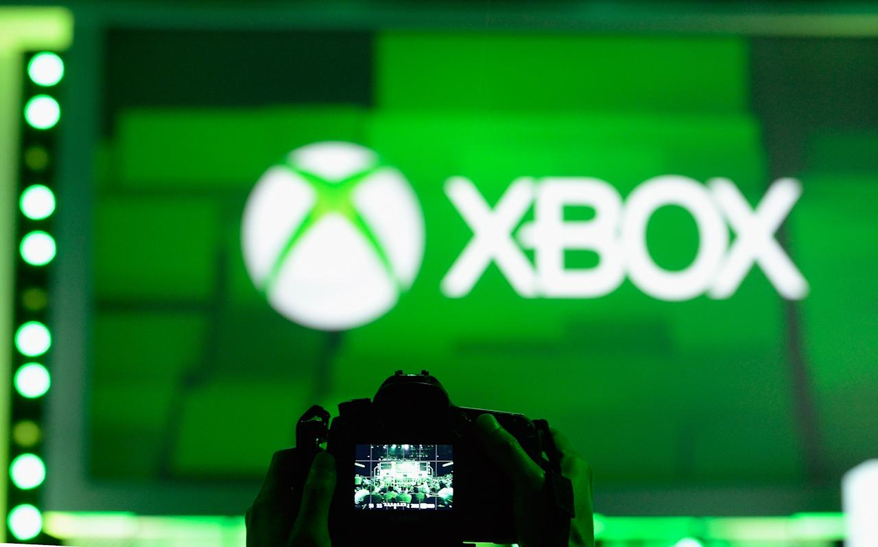 LOS ANGELES, CA - JUNE 10:  An attendee takes a photo of the XBOX logo during the Microsoft Xbox news conference at the Electronic Entertainment Expo at the Galen Center on June 10, 2013 in Los Angeles, California. Thousands are expected to attend the annual three-day convention to see the latest games and announcements from the gaming industry. (Photo by Kevork Djansezian/Getty Images)