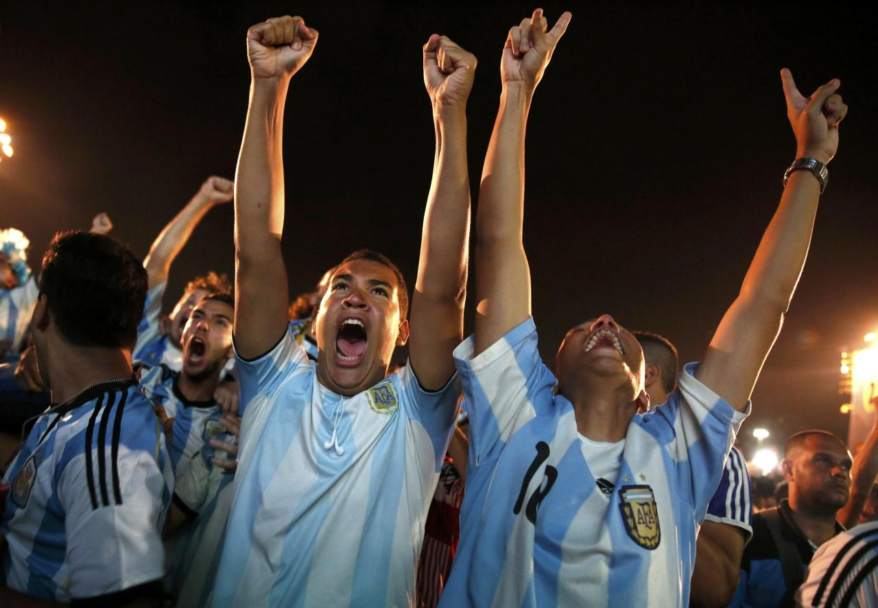 Argentinian soccer fans react during the penalty shootout as they watch a broadcast of the 2014 World Cup semi-final against the Netherlands at Copacabana beach in Rio de Janeiro, July 9, 2014. REUTERS/Pilar Olivares (BRAZIL - Tags: SOCCER SPORT WORLD CUP TPX IMAGES OF THE DAY)