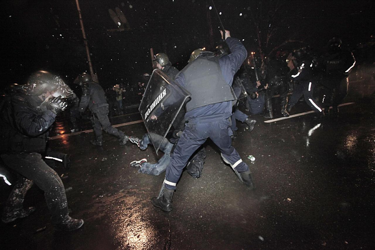 Protesters are beaten and detained by riot police during a protest against high electricity prices in Sofia, on late Tuesday, Feb. 19, 2013. Bulgaria's prime minister announced on Tuesday that the license held by a Czech company for power distribution in parts of the Balkan country will be revoked following protests against high electricity prices. (AP Photo/Valentina Petrova)