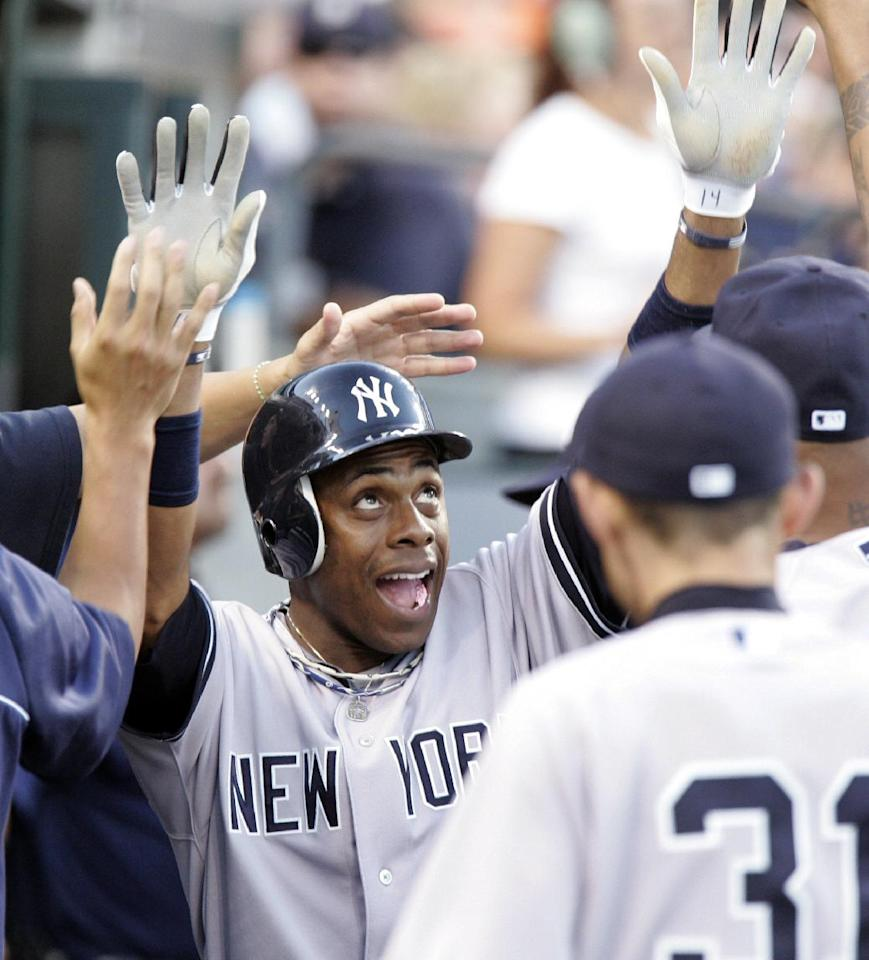 FILE - In this Aug. 6, 2012 file photo, New York Yankees' Curtis Granderson celebrates in the dugout after scoring on a double by Robinson Cano in the fifth inning of a baseball game against the Detroit Tigers, in Detroit. A person familiar with the situation says free-agent outfielder Granderson and the New York Mets have agreed to a $60 million, four-year contract. The person spoke to The Associated Press on condition of anonymity Friday, Dec. 6, 2013, because the deal was pending a physical and no announcement had been made. (AP Photo/Duane Burleson, File)