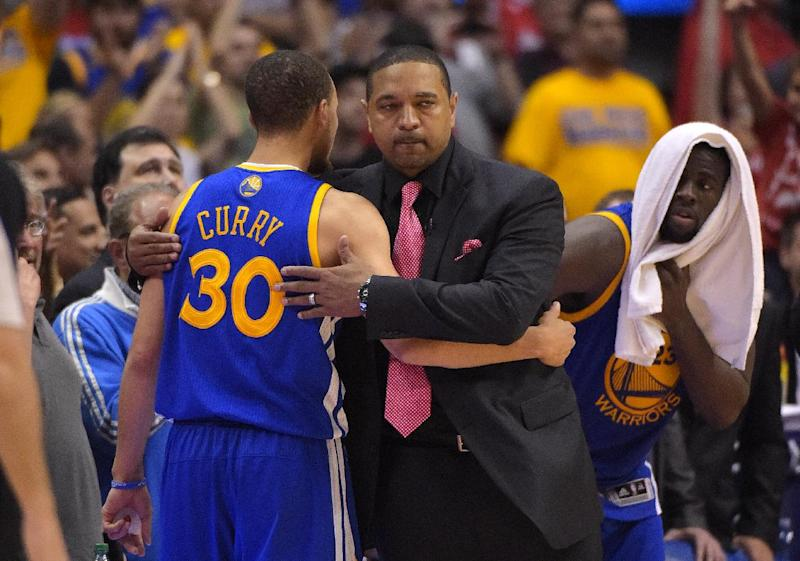 Golden State Warriors head coach Mark Jackson, center, hugs guard Stephen Curry after Curry was taken out of the game as forward Draymond Green looks on during the second half in Game 7 of an opening-round NBA basketball playoff series, Saturday, May 3, 2014, in Los Angeles. The Clippers won 126-121