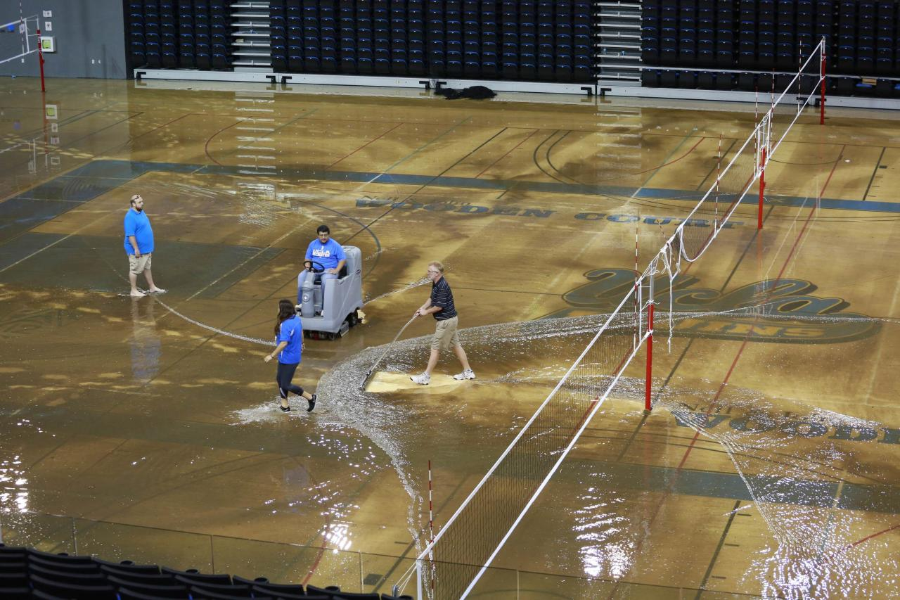 Workers try to clear water from the floor of Pauley Pavillion on the UCLA campus from a broken thirty inch water main, which gushed water onto Sunset Boulevard in the Westwood section of Los Angeles July 29, 2014. The geyser from the 100-year old water main flooded parts of the campus and stranded motorists on surrounding streets. REUTERS/Jonathan Alcorn (UNITED STATES - Tags: ENVIRONMENT DISASTER)