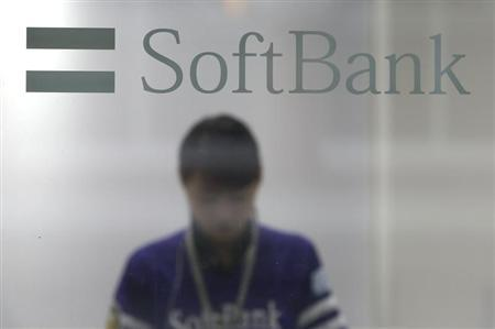 A shop clerk is seen through a window displaying a logo of SoftBank Corp at its branch in Tokyo