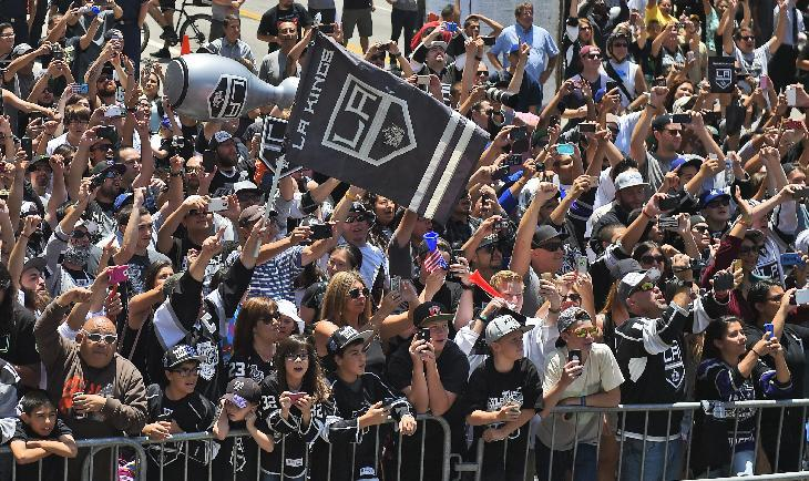 Fans of the Los Angeles Kings NHL hockey team cheer as the team rides by with the Stanley Cup trophy during a parade, Monday, June 16, 2014, in Los Angeles. The parade and rally were held to celebrate the Kings' second Stanley Cup championship in three seasons. The Kings defeated the New York Rangers for the title