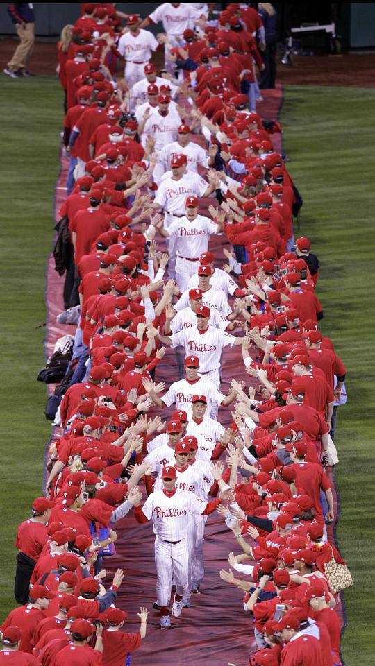 Led by pitcher Jamie Moyer, the Philadelphia Phillies are greeted as they pass through two rows of fans in center field during opening night ceremonies before the start an MLB baseball game against the Atlanta Braves, Sunday, April 5, 2009, in Philadelphia. (AP Photo/Tom Mihalek)