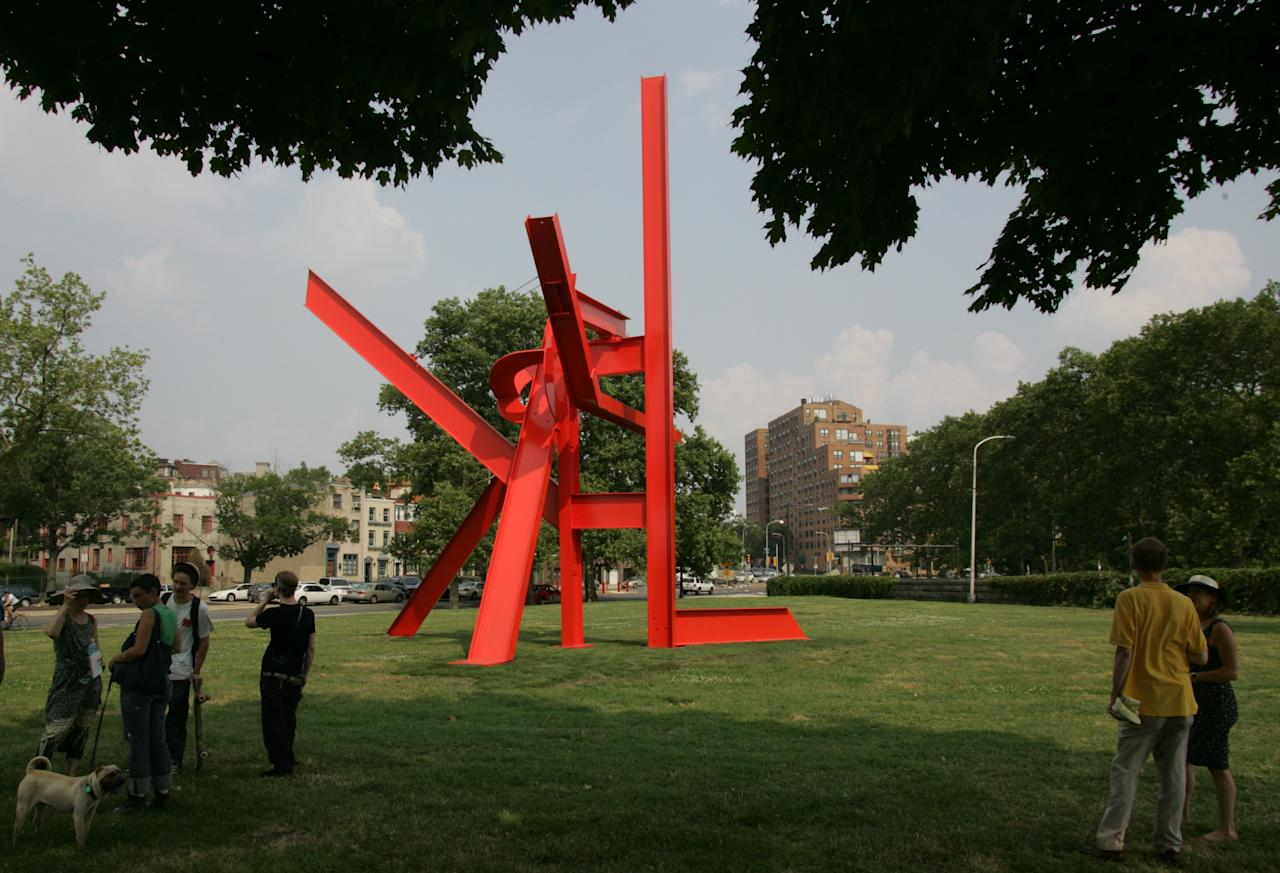 """People look at """"Iroquois,"""" a 40-foot sculpture by Mark di Suvero, before ceremonies as the Fairmount Park Art Association dedicated it on Wednesday, June 27, 2007, in Philadelphia. (AP Photo/George Widman)"""