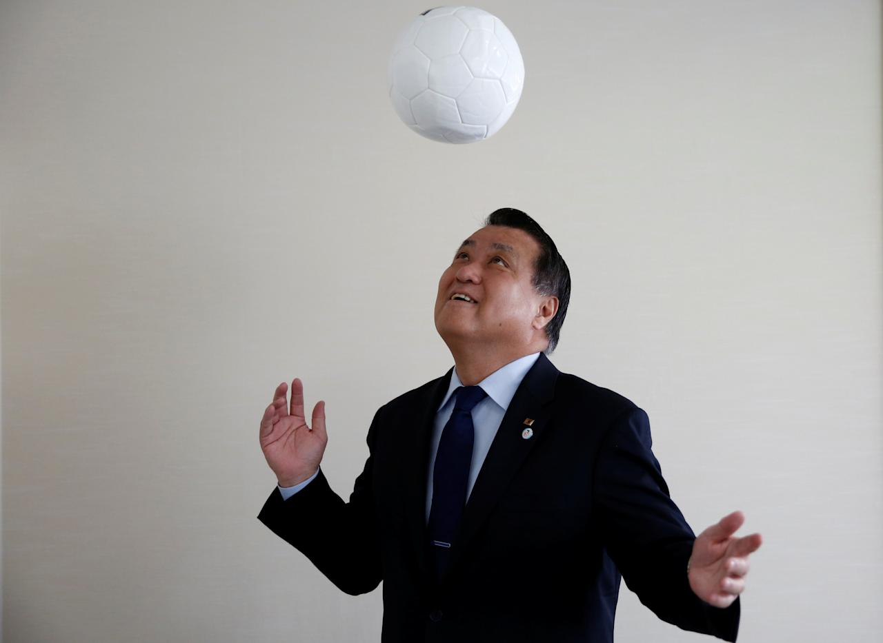 Japan Football Association (JFA) President Kozo Tashima makes a header with a soccer ball as he poses to a photographer after an interview with Reuters at his office in Tokyo, Japan, January 12, 2017. REUTERS/Kim Kyung-Hoon