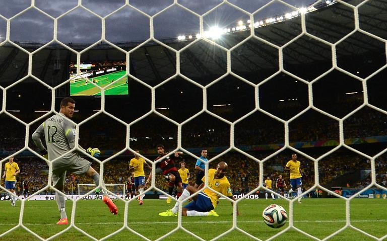 Brazil's goalkeeper Julio Cesar (left) concedes a goal to Germany's midfielder Sami Khedira (back centre) during the semi-final match at the Mineirao Stadium in Belo Horizonte during the 2014 FIFA World Cup on July 8, 2014